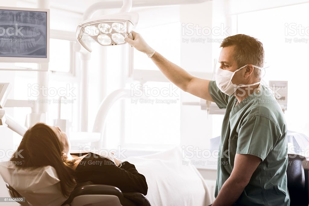 Dentist adjusting electric lamp over patient in clinic stock photo