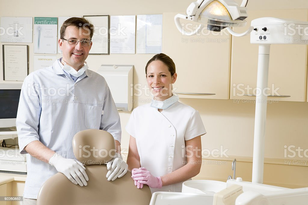 Dentist and assistant in exam room royalty-free stock photo