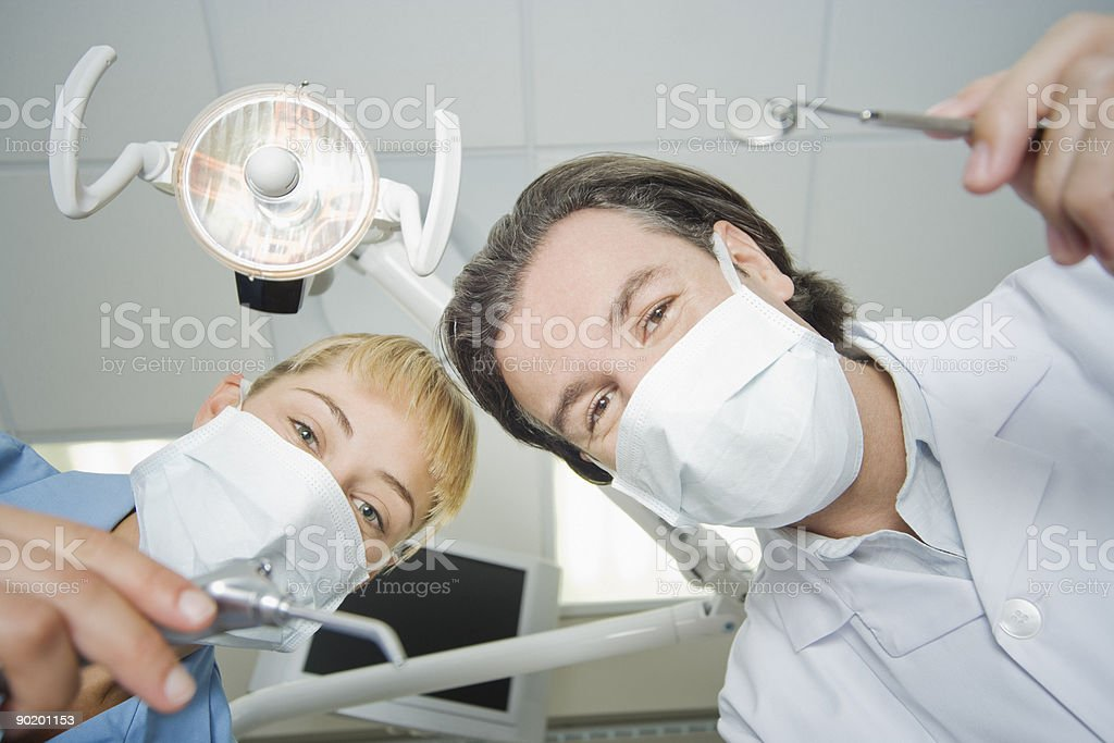 Dentist and assistant leaning down to work on patient royalty-free stock photo