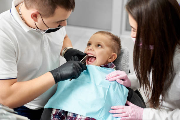 Dentist and assistant pull the tooth to the baby with forceps. The child looks at the doctor without fear. Modern medicine stock photo