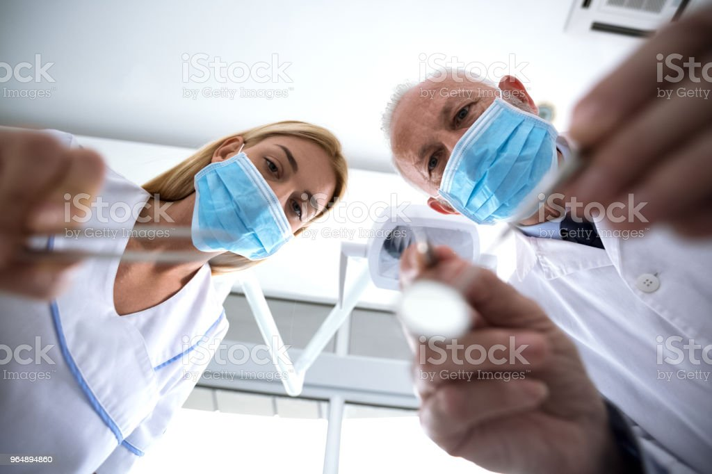 Dentist and assistant with sterile mask examine teeth of patient royalty-free stock photo