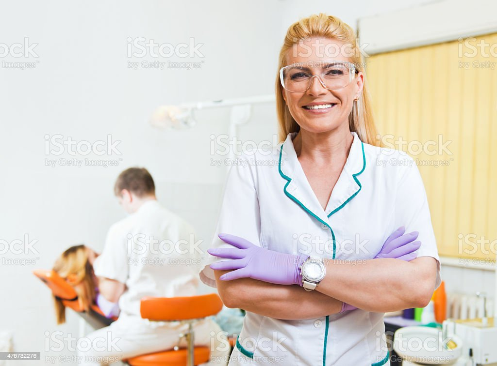 Dentist and her assistant examining teeth at dental office stock photo