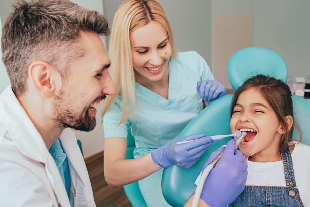 zahnarzt und seine assistentin behandeln die zähne eines kleinen mädchens. pädiatrische zahnheilkunde - sprechstundenhilfe stock-fotos und bilder