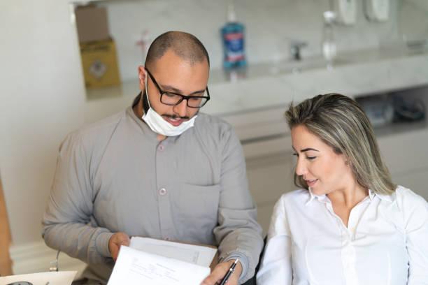 tandläkare och patient i en tandläkare kontor - two dentists talking bildbanksfoton och bilder