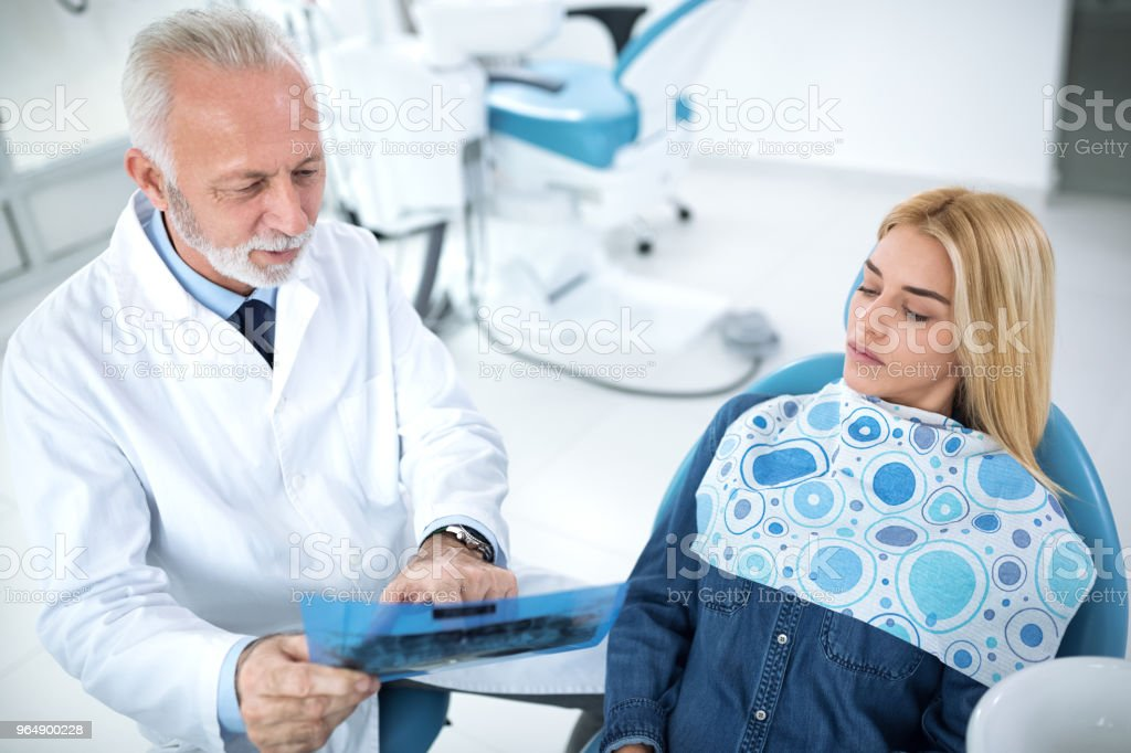 Dentist and patient looking at x-ray of teeth royalty-free stock photo