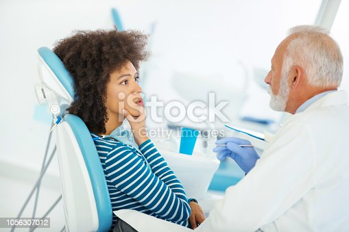 Closeup of a mid 50's male dentist examining an early 30's African american patient. She's having some pains in her lower teeth and jay.