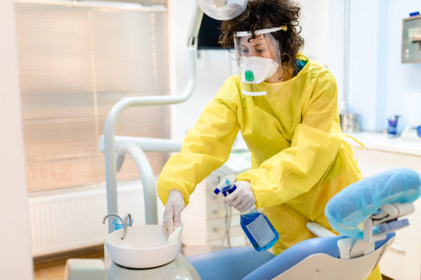Dentist assistant using strong disinfectant agent to clean dental office for the next patient stock photo