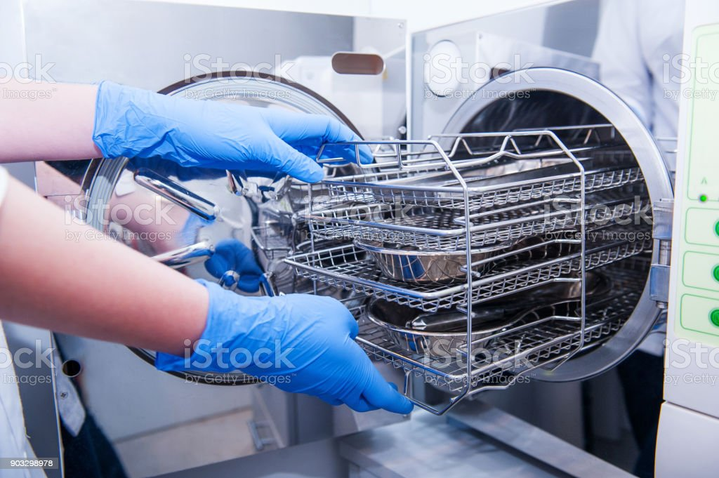 Dentist assistant's hands get out sterilizing medical instruments from autoclave. Selective focus stock photo