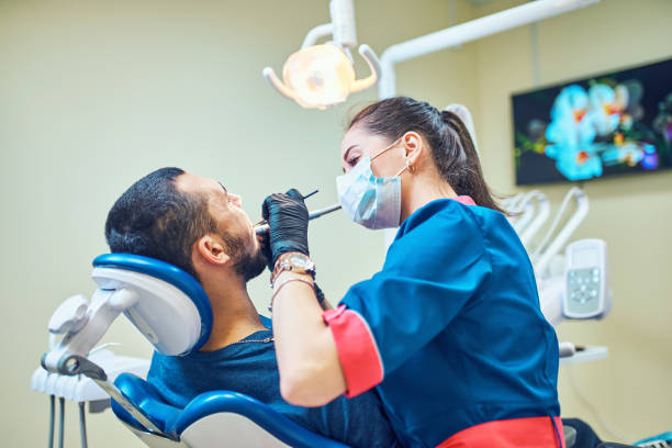 Dentist at work on a patient in clinic stock photo