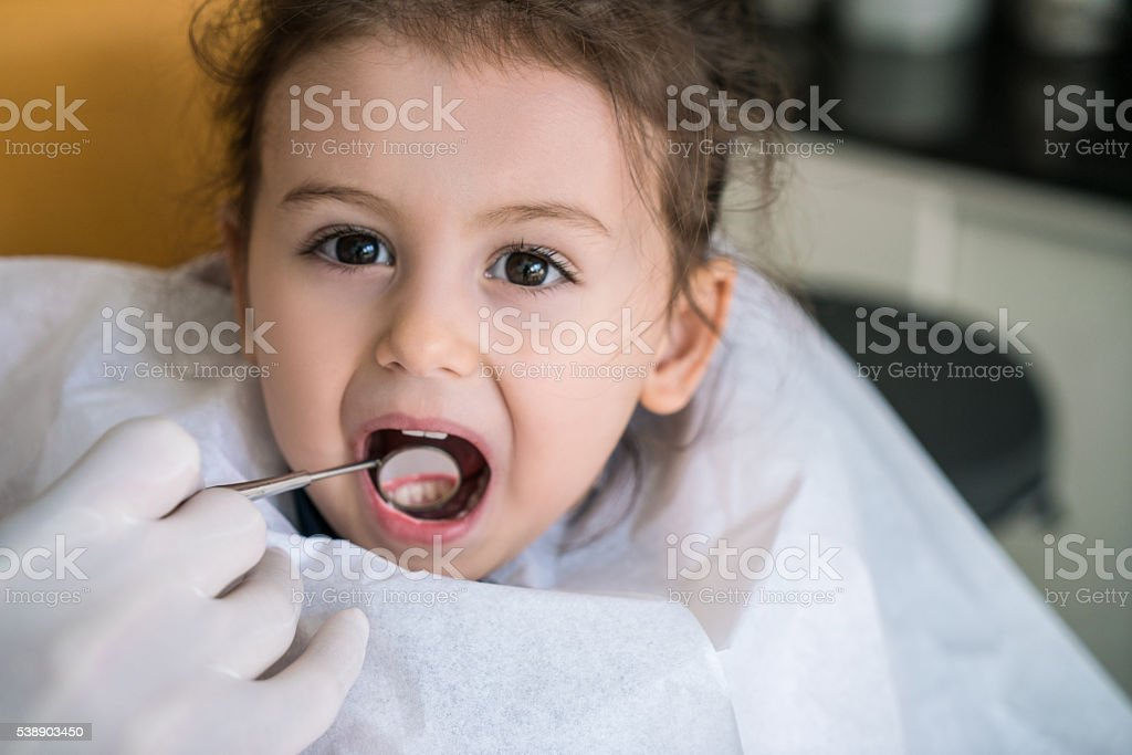Dentist checking girl's teeth stock photo