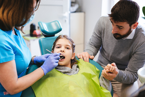 Dentist checking girl's teeth while her dad is holding her hand.