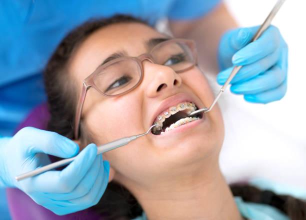 Dentist checking little girl's dental braces stock photo