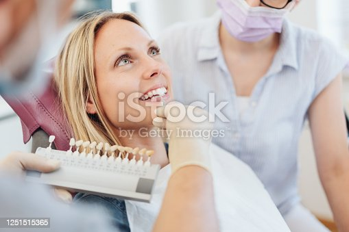 Dentist checking the whiteness of a patients teeth against color coded samples during an examination in his surgery
