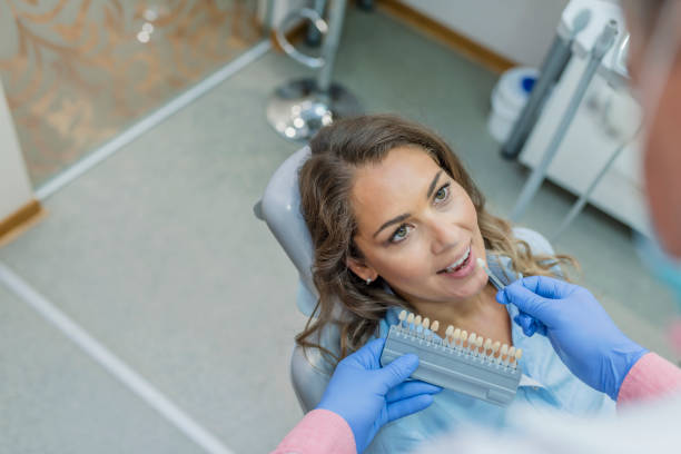 Dentist choosing the color of teeth Close up portrait of mature brown hair women in dentist chair, Check and select the color of the teeth. Dentist makes the process of treatment in dental clinic office. Photo of  Dentist curing Caucasian female patient, Woman having teeth examined at clinic tooth crown stock pictures, royalty-free photos & images