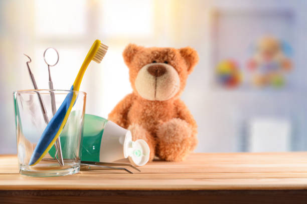 Dentist concept for children with tools in glass cup stock photo
