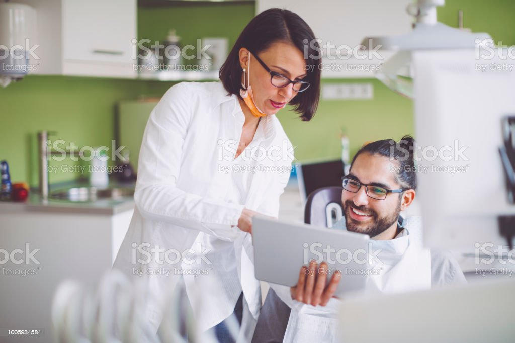 Dentist consulting her patient stock photo