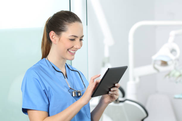 Dentist consulting online information in a tablet stock photo