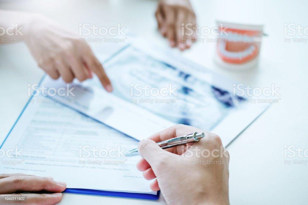 Dentista, consulta con el paciente que presenta resultados en la película de radiografía Dental acerca del problema del paciente foto de stock libre de derechos