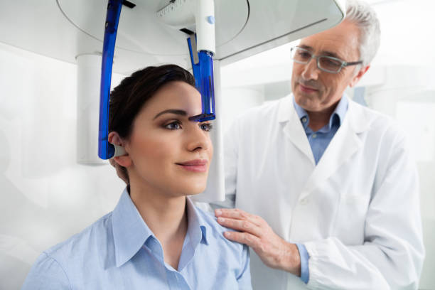 A dentist controlling his female patient before an x-ray panoramic digital stock photo