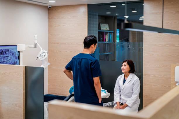 tandläkare diskuterar med manlig assistent på kliniken - two dentists talking bildbanksfoton och bilder