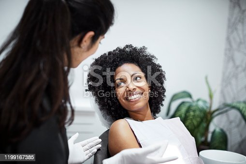 Smiling woman listening to dental doctor. Female dentist is discussing with patient. They are in clinic.