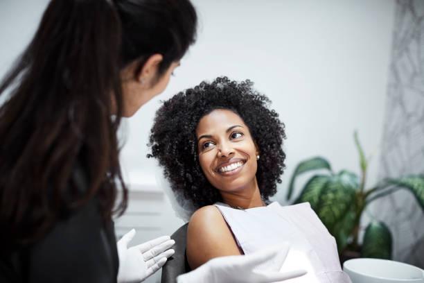 dentist discussing with smiling female patient - dentist zdjęcia i obrazy z banku zdjęć