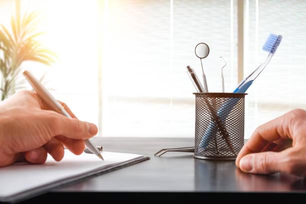 Médico dentista escribiendo en su escritorio con cortinas y fondo de la planta - foto de stock