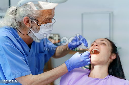 dentist  doing oral checkup of oral cavity