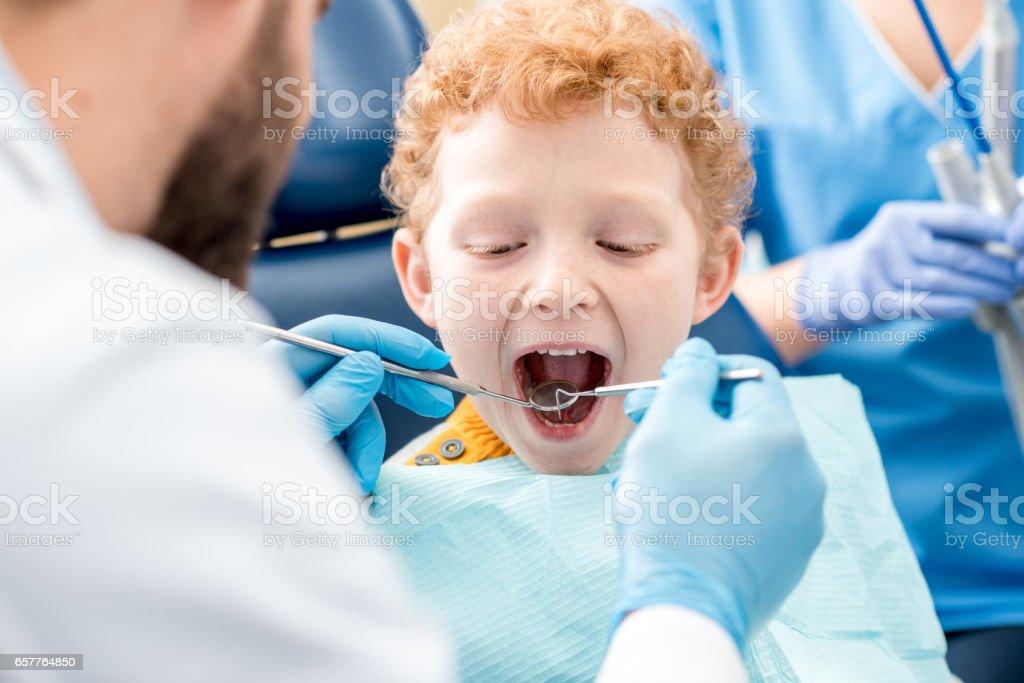 Dentist examinating boy's teeth stock photo