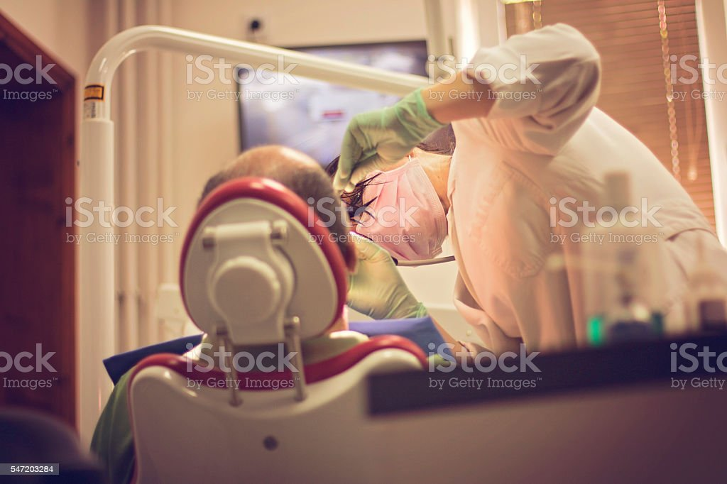Dentist examines the teeth of patient stock photo