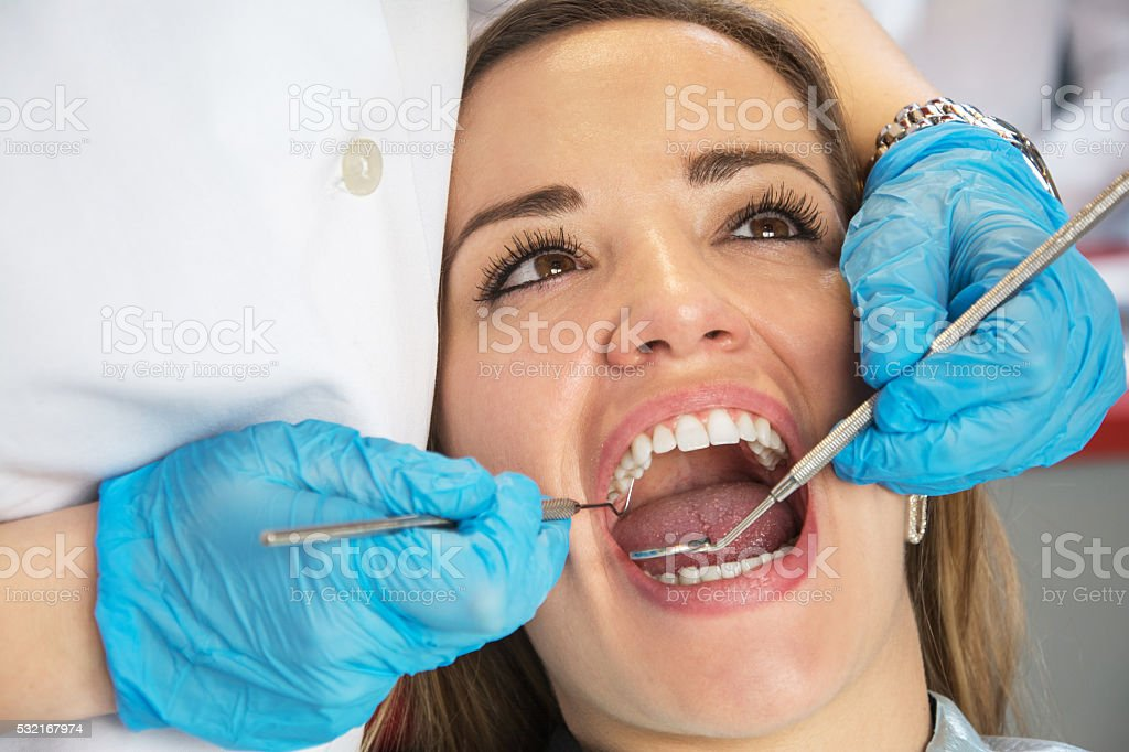 Dentist examining a patient's teeth in the dental office. stock photo