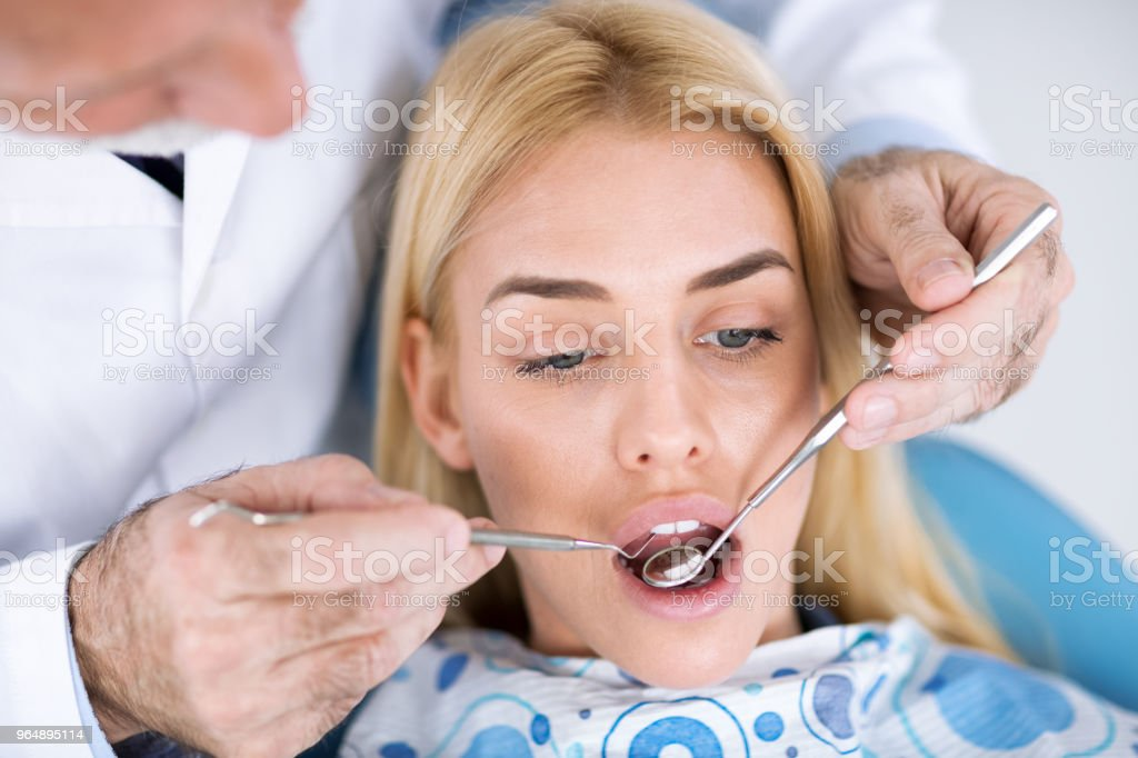 Dentist examining a patient's teeth in the dentist royalty-free stock photo