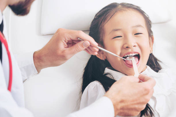 dentist examining child teeth in dental clinic. - dentista foto e immagini stock