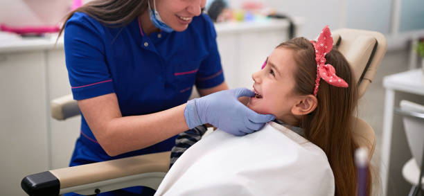 dentist examining his girl patient in dentist's stock photo