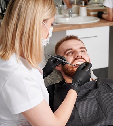 Dentist examining male patient teeth in dental clinic.