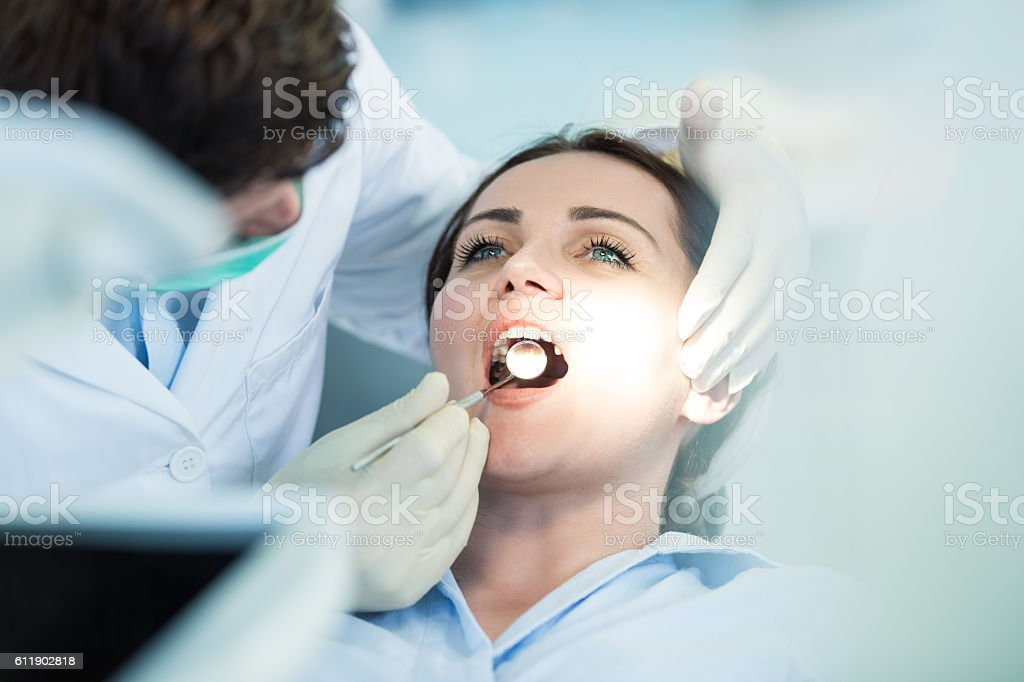 Dentist examining Patient teeth with a Mouth Mirror. Dentist examining Patient teeth with a Mouth Mirror. Dentist is a Man, Patient is a Woman. Patient is Relaxed and not scared of Dentist. Dentist Stock Photo
