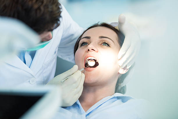 Dentist examining Patient teeth with a Mouth Mirror. stock photo