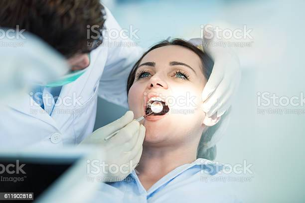 Dentist Examining Patient Teeth With A Mouth Mirror Stock Photo - Download Image Now