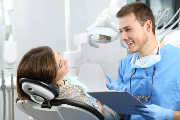 dentist explaining dental treatment procedure to a patient - dental assistant stock photos and pictures