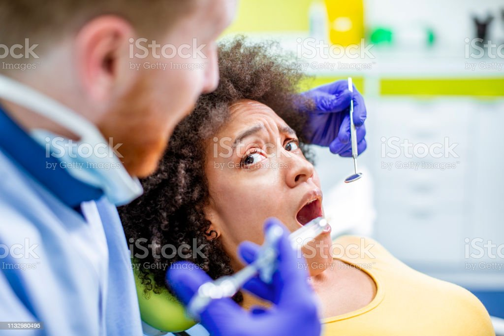 Dentist Giving A Patient A Local Dental Anesthesia Using A Syringe