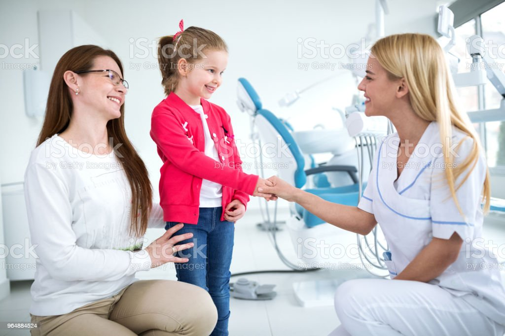 Dentist greeted girl and her mom royalty-free stock photo