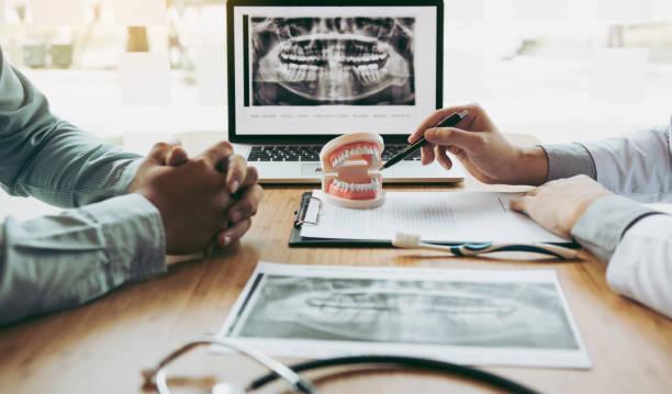 zahnarzt hand zeigen röntgenbild in laptop-computer und sprechen mit dem patienten über medikamente und chirurgische behandlung. - kieferorthopäde stock-fotos und bilder