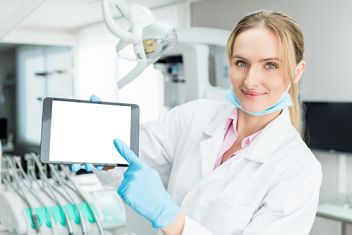 928855610 istock photo Dentist holding blank screen digital tablet 651316348