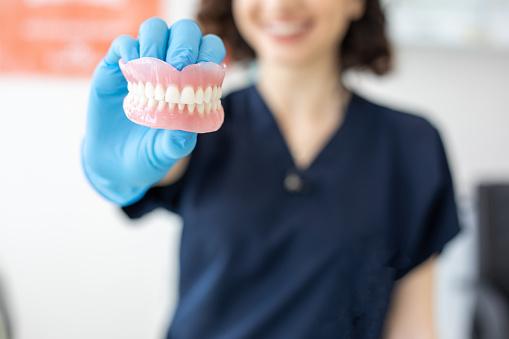 istock Dentist holding denture 1035421864