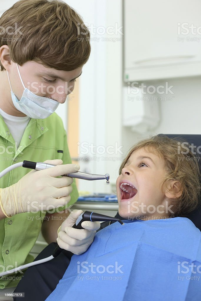Dentist holds grinding drill, girl opens her mouth royalty-free stock photo