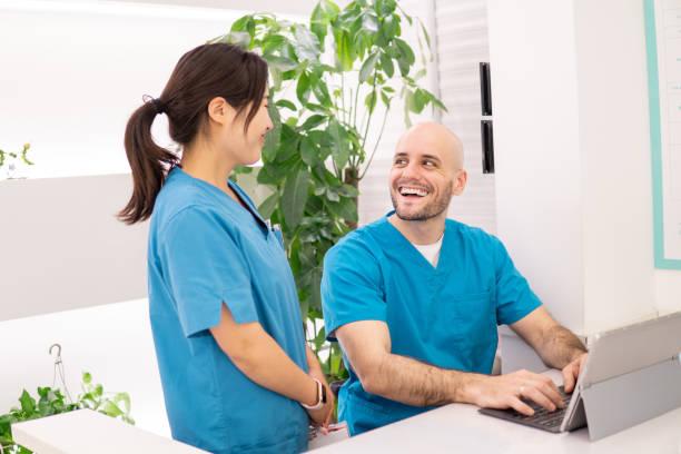 tandläkare i sin klinik pratar med sin assistent - two dentists talking bildbanksfoton och bilder