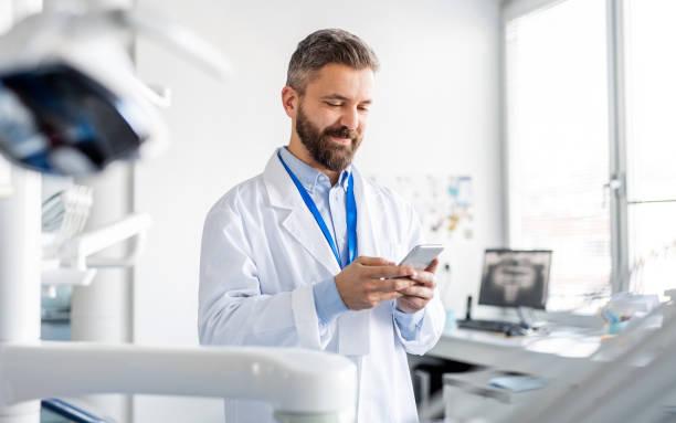 Zahnarzt in der modernen Zahnchirurgie, mit Smartphone. – Foto
