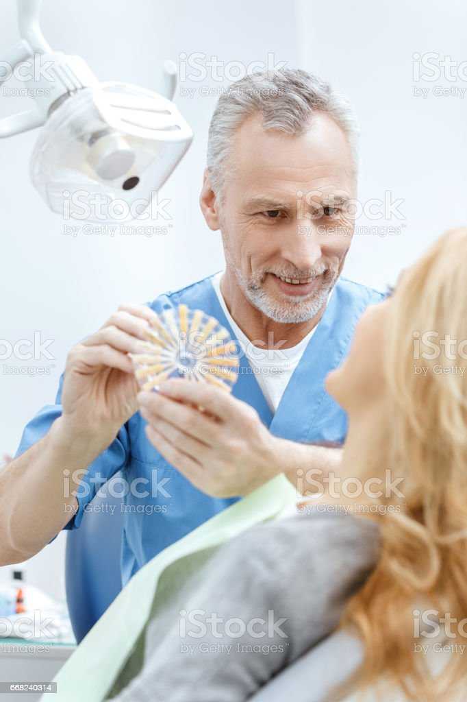 dentist matching teeth colour with palette in dental clinic foto stock royalty-free