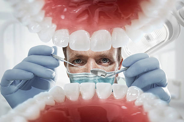 Dentist over open patient's mouth looking in teeth. Inside vew Close-up of patient's open mouth during oral inspection with mirror and hook mouth stock pictures, royalty-free photos & images