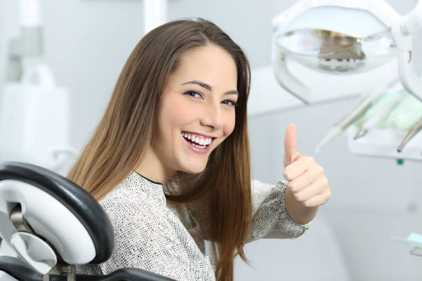 Dentist patient satisfied after treatment Patient with perfect white teeth and smile satisfied after dental treatment in a dentist office with medical equipment in the background implant stock pictures, royalty-free photos & images